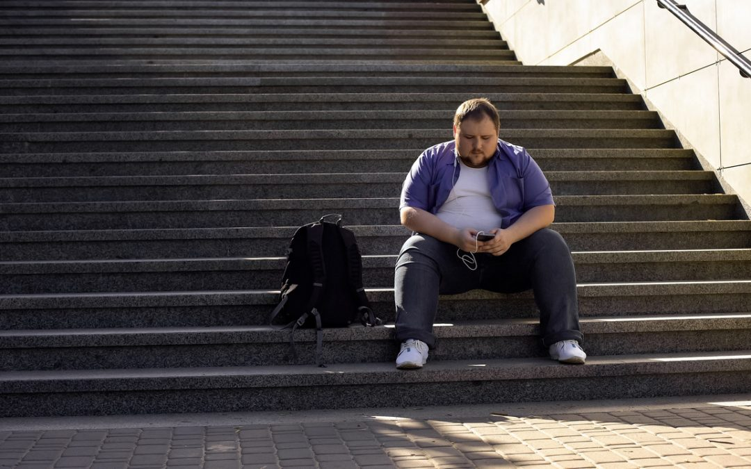 Ein mehrgewichtiger Mann, ca. 25-30 Jahre alt, sitzt auf einer Treppe. Er trägt ein weißes T-Shirt, ein offenes, einfarbiges blau-lilanes Hemd und eine dunkelblaue Jeans. Er sitzt auf den unteren Stufen einer grauen Treppe und schaut auf sein Smartphone. Neben ihm steht ein schwarzer Rucksack. Vermutlich wartet er und nutzt die Zeit, auf sein Smartphone zu schauen. Er sieht entspannt, aber nicht losgelöst oder glücklich aus. Sein Blick ist nach unten gerichtet. Ein Kabel schlängelt sich vom Smartphone zu einem Kopfhörer im Ohr des Mannes.